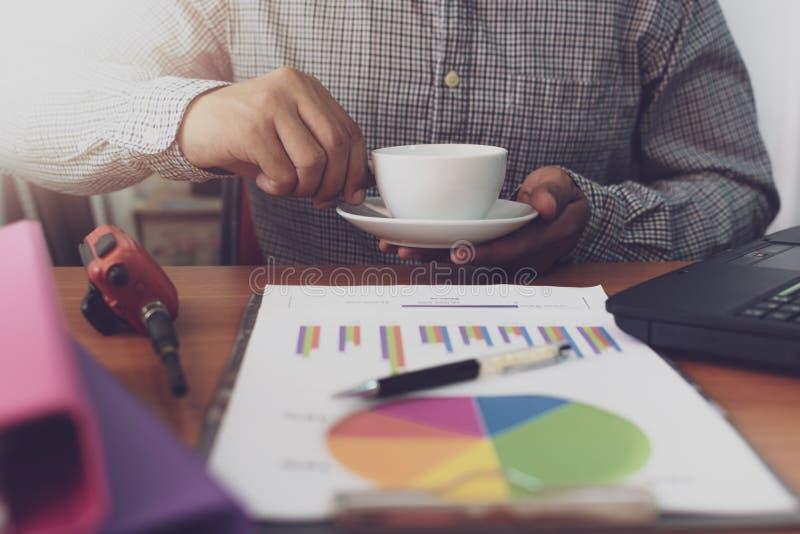 Affärsman som rymmer kaffekoppen, medan arbeta på kontorsskrivbordet royaltyfri fotografi