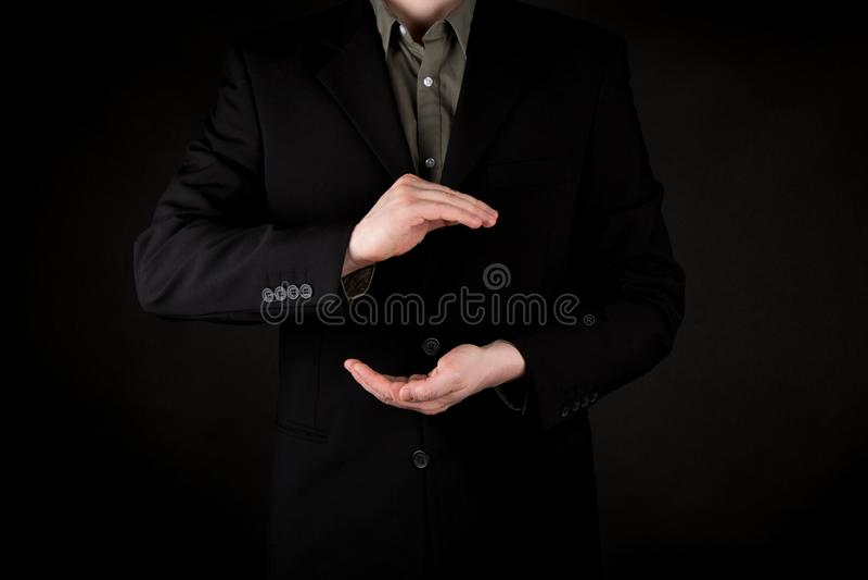 Affärsman som rymmer något med båda händer, svart följe och lutningsvartbakgrund arkivfoton