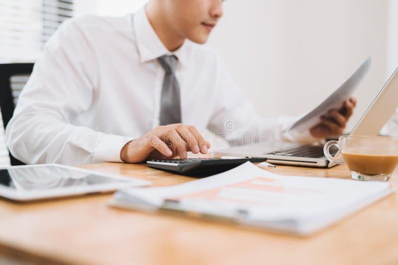 Affärsman som rymmer papper, upptaget arbete på bärbar datordatoren och använder för att beräkna i det moderna kontoret, slut upp arkivbild