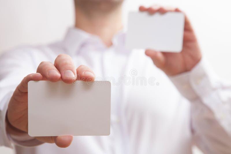 Affärsman som rymmer två tomma affärskort arkivfoton