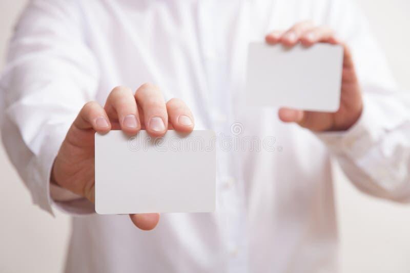 Affärsman som rymmer två tomma affärskort royaltyfri foto
