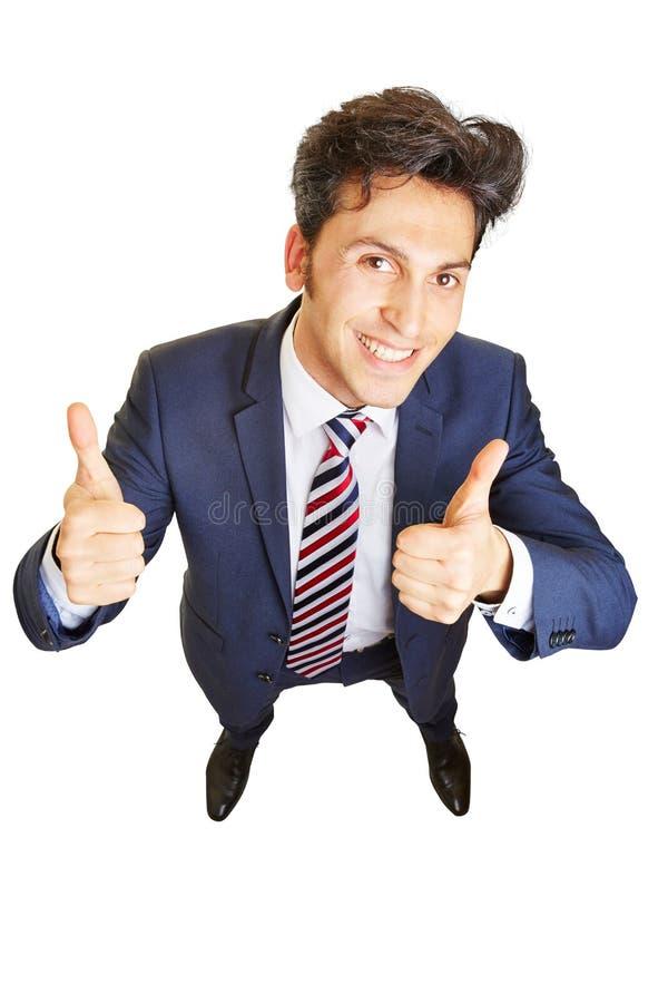 Affärsman som rymmer upp båda tummar arkivbilder