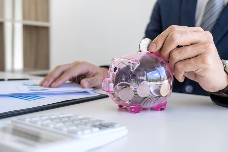 Affärsman som sätter mynt in i spargrisen och använder räknemaskin t arkivfoto