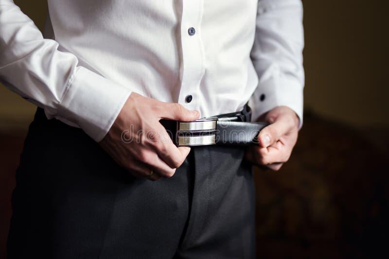 Affärsman som sätter på ett bälte, mode och beklär begreppet, groo royaltyfri foto