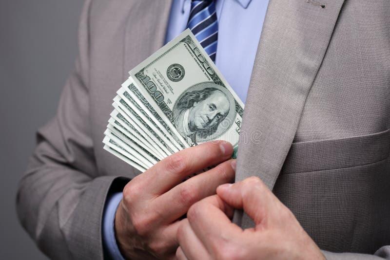 Affärsman som sätter pengar i fack arkivfoto