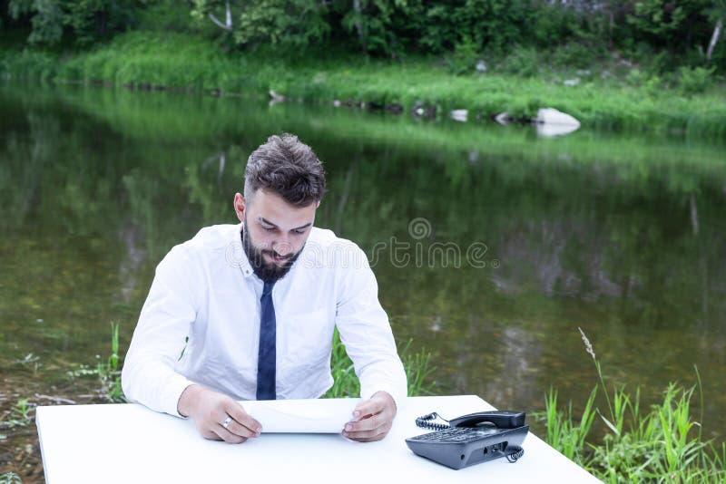 Affärsman som söker efter bedrägeri och kontraktsfel Ung skäggsarbetare som läser dokument arkivfoto