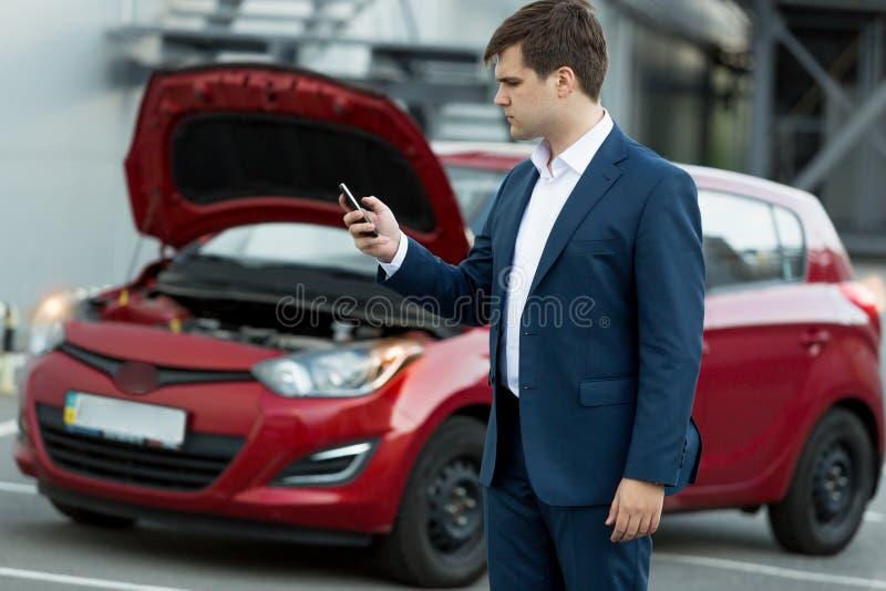 Affärsman som söker i mobiltelefon hur man reparerar bilen arkivfoton