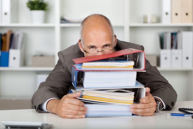 Affärsman som ser över en bunt av limbindningar arkivfoton