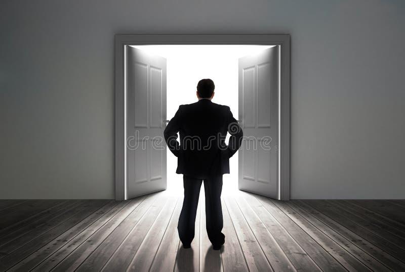 Affärsman som ser dörren som visar ljust ljus royaltyfri fotografi