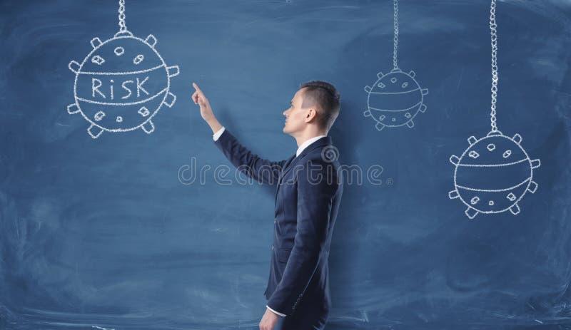 Affärsman som ser de sjö- minerna och ord`-risken `` som dras med krita på mörkret - blå vägg royaltyfri illustrationer