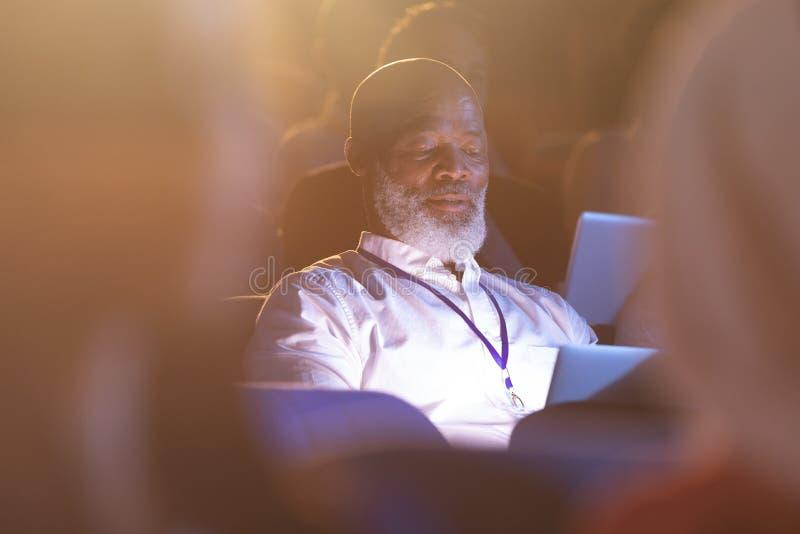 Affärsman som ser den digitala minnestavlan, medan sitta i salongen royaltyfri foto
