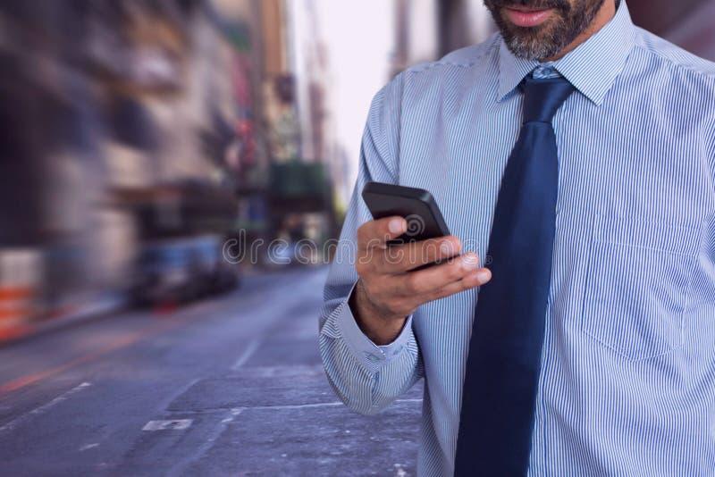 Affärsman som ser en telefon mot stadsbakgrund arkivbilder