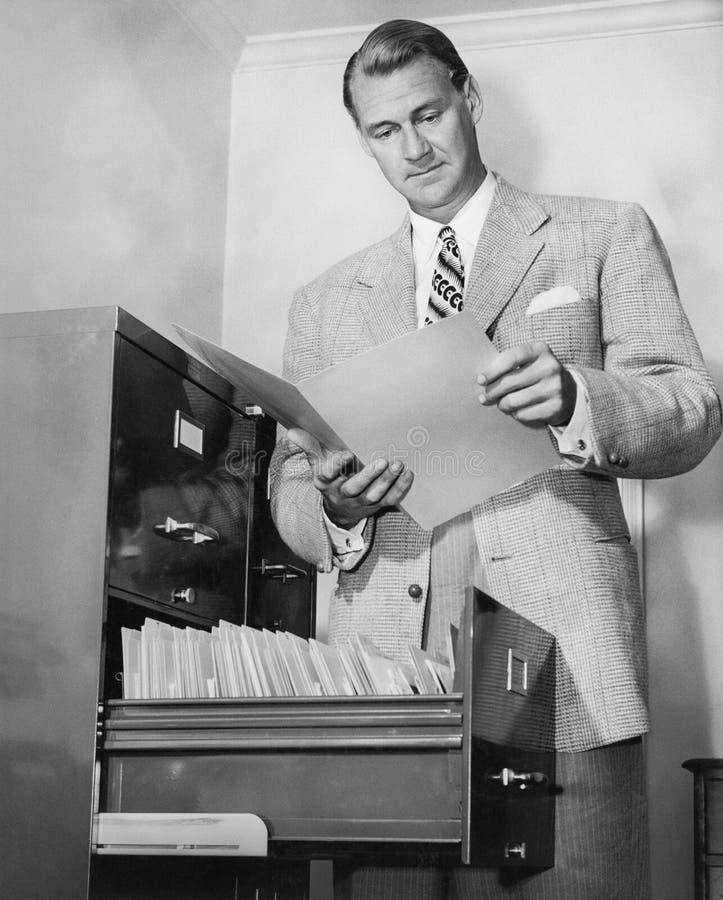 Affärsman som ser ett papper bredvid en dokumentskåp (alla visade personer inte är längre uppehälle, och inget gods finns Supplie royaltyfri foto
