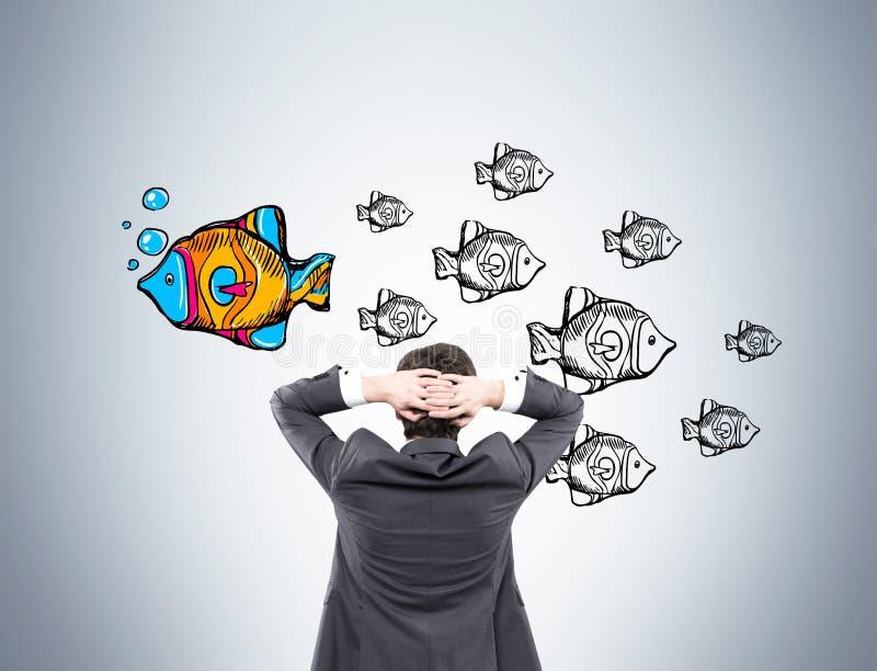 Affärsman som ser fisken på den gråa väggen royaltyfri bild