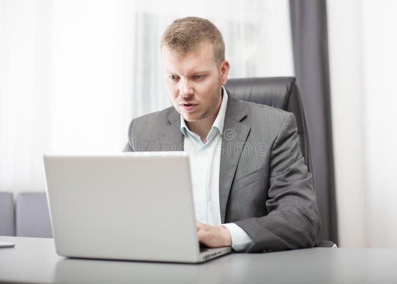 Affärsman som ser hans bärbar dator i misstro royaltyfri foto