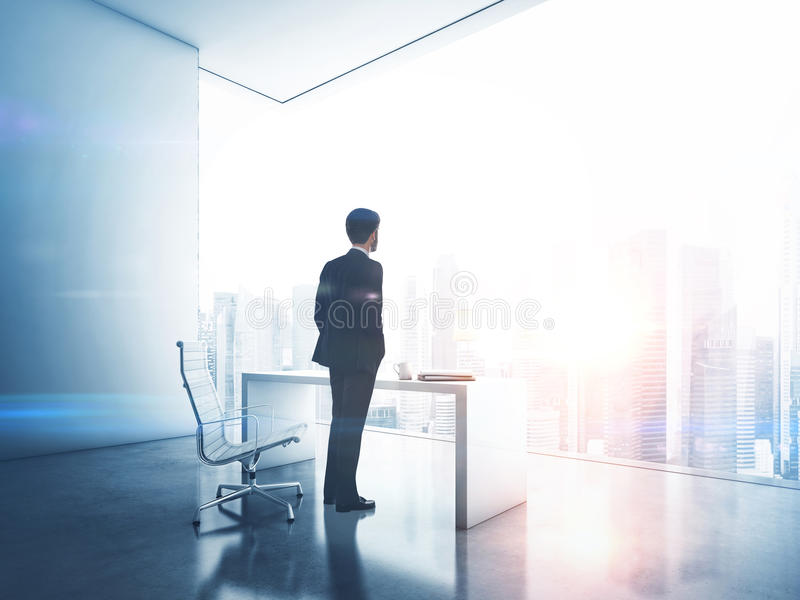 Affärsman som ser megalopolisen till och med fönster arkivfoto