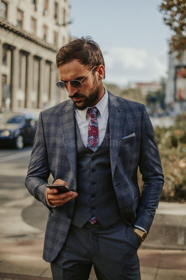 Affärsman som ser mobiltelefonen, medan stå i gatan arkivbild