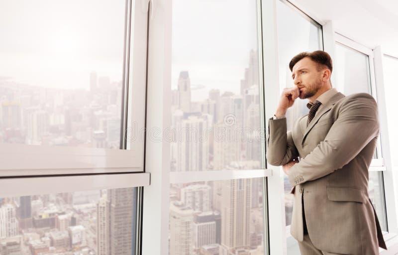 Affärsman som ser staden från hans kontor royaltyfri fotografi
