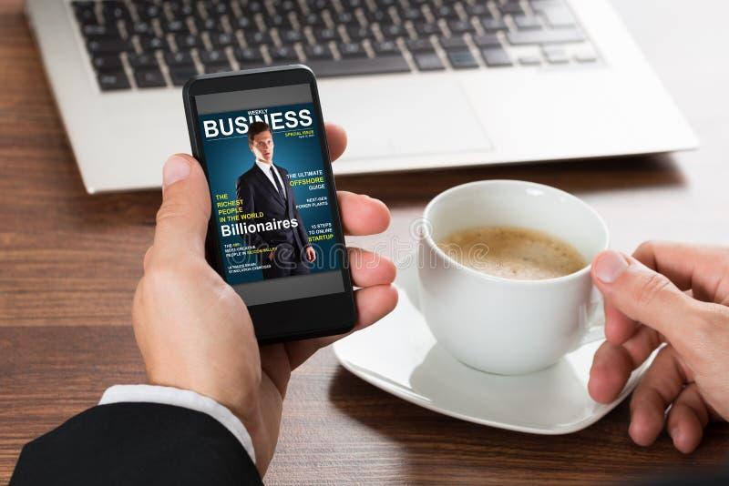 Affärsman som ser tidskriften på mobiltelefonen royaltyfria foton