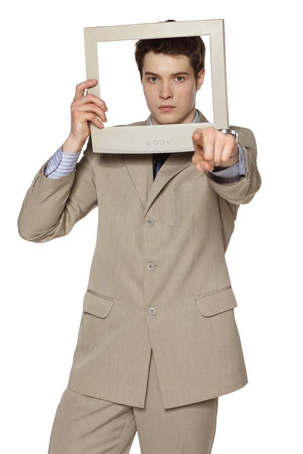 Affärsman som ser till och med den TV-/datorskärmen som pekar på kameran royaltyfri foto