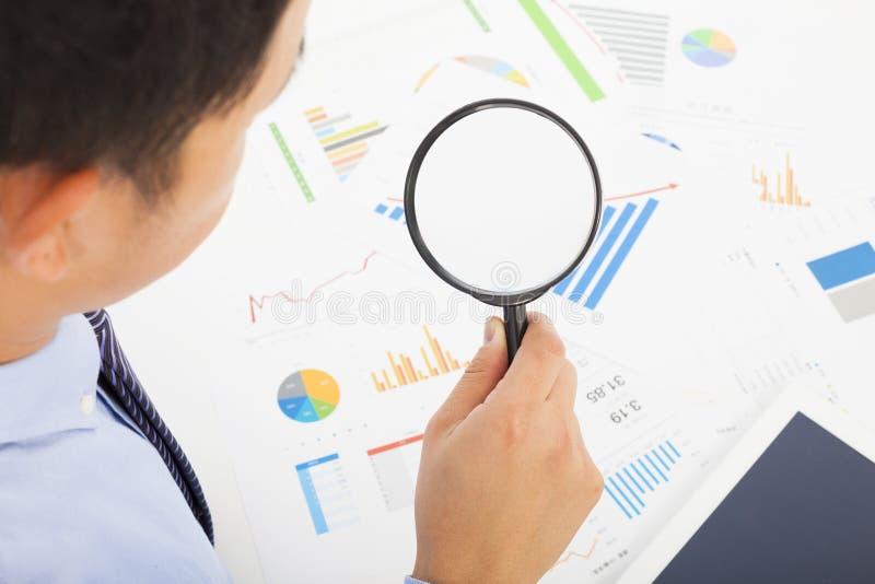 Affärsman som ser till och med förstoringsapparatexponeringsglas till dokument arkivbild
