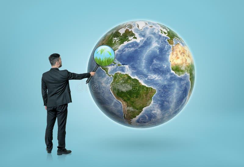 Affärsman som ser till och med förstoringsglaset på jorden och ser gräs royaltyfri bild