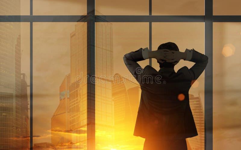 Affärsman som ser ut ur hans kontorsfönster royaltyfria bilder