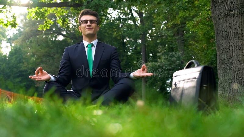 Affärsman som sitter på gräs och mediterar i ny luft, energi av naturen royaltyfri bild