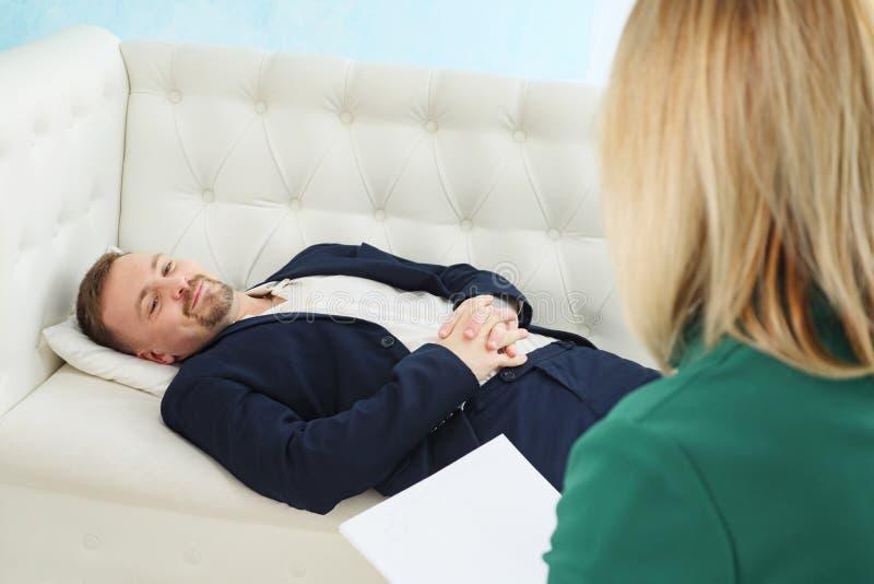 Affärsman som sitter på soffan som talar till hans terapeut på terapiperioden arkivbilder