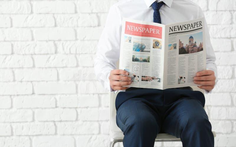 Affärsman som sitter på stol, medan läsa tidningen mot bakgrund för tegelstenvägg arkivfoton