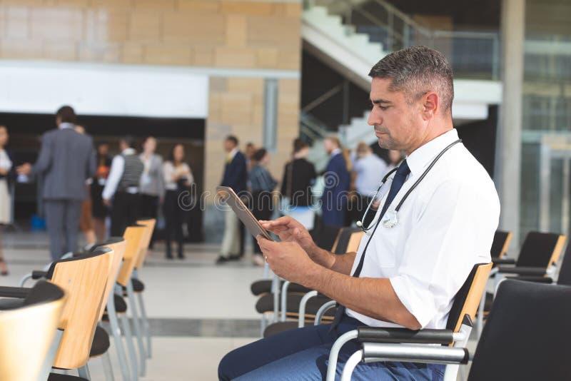 Affärsman som sitter på stol och använder den digitala minnestavlan i ett väntande rum arkivbild