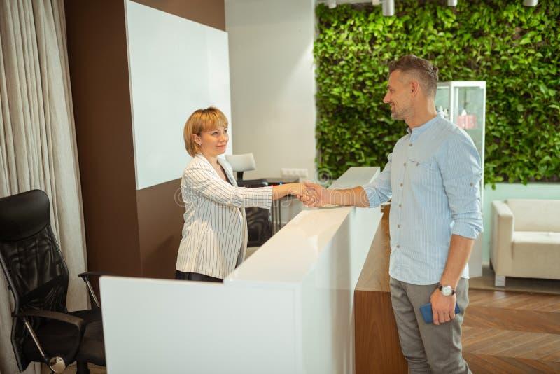 Affärsman som skakar handen av administratören, medan komma till arkivfoto
