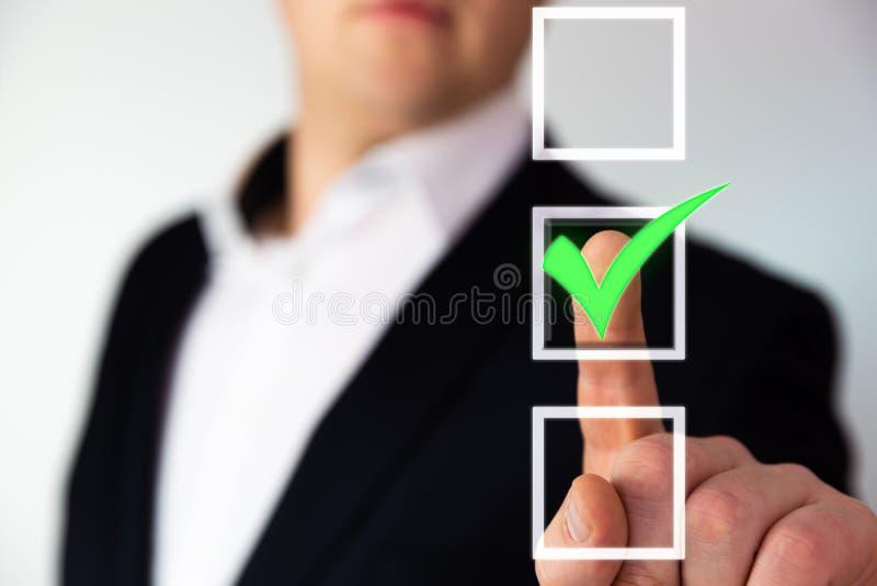 Affärsman som skjuter checkboxknappen med en grön fästing arkivbilder