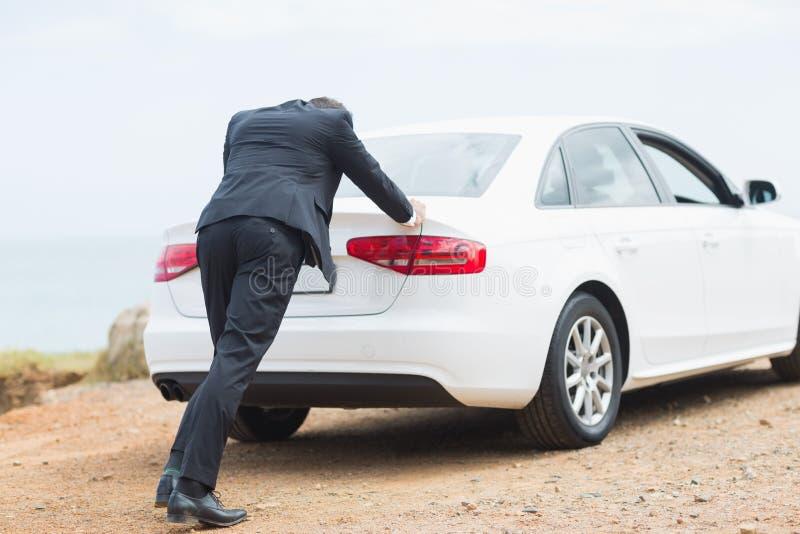 Affärsman som skjuter hans bil royaltyfri fotografi