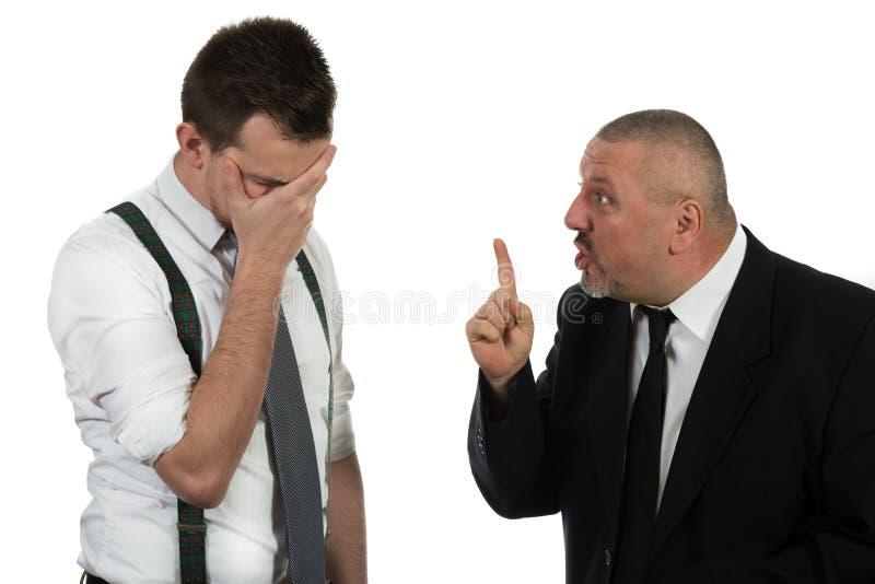 Affärsman som skriker och slåss på en ung kollega arkivbild