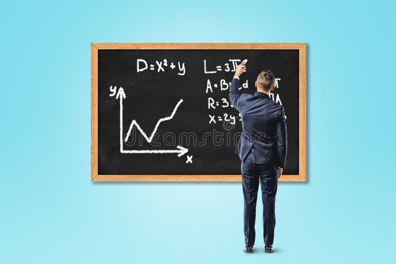 Affärsman som skriver formel på den svart tavlan eller svart tavla på blå bakgrund arkivfoton