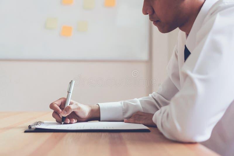 Affärsman som skriver formen för att sända för att återuppta arbetsgivaren för att granska platsansökan royaltyfri foto