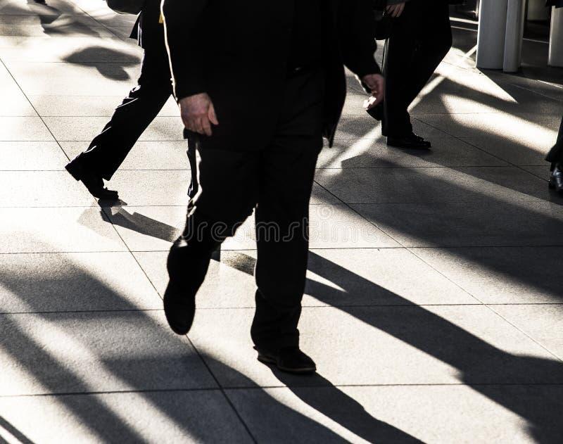Affärsman som snabbt går på stadstrottoaren som bär den svarta dräkten silhouetted i solen med långa mörka skuggor och ljust ljus arkivbilder