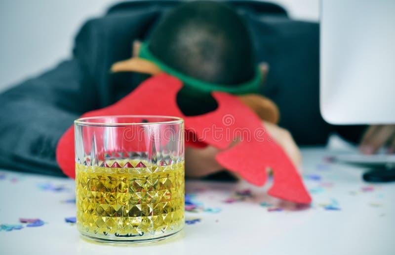 Affärsman som sover i hans kontor efter ett julparti royaltyfri fotografi