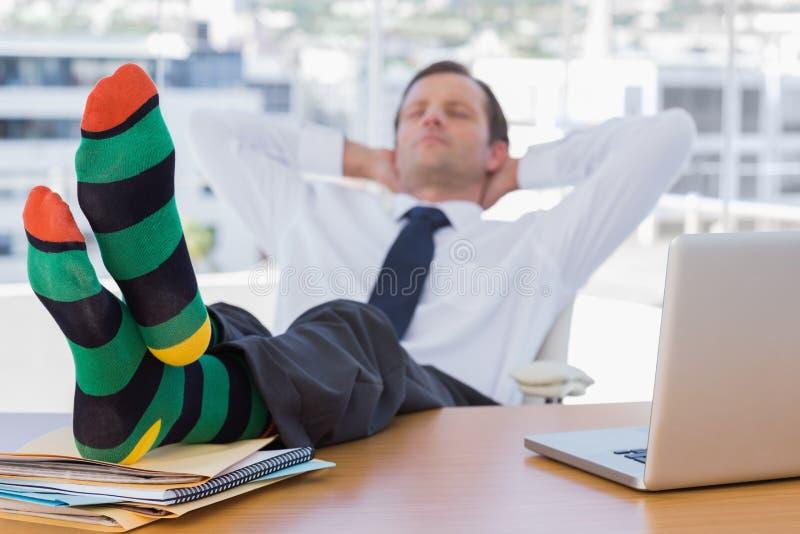 Affärsman som sover med fot på hans skrivbord fotografering för bildbyråer