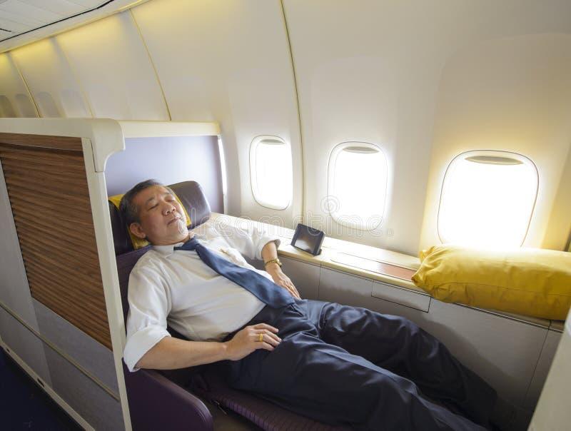 Affärsman som sover på första klass av flygplanet i bekväm enkel plats royaltyfria bilder