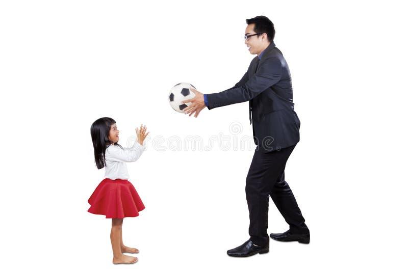 Affärsman som spelar bollen med hans dotter fotografering för bildbyråer