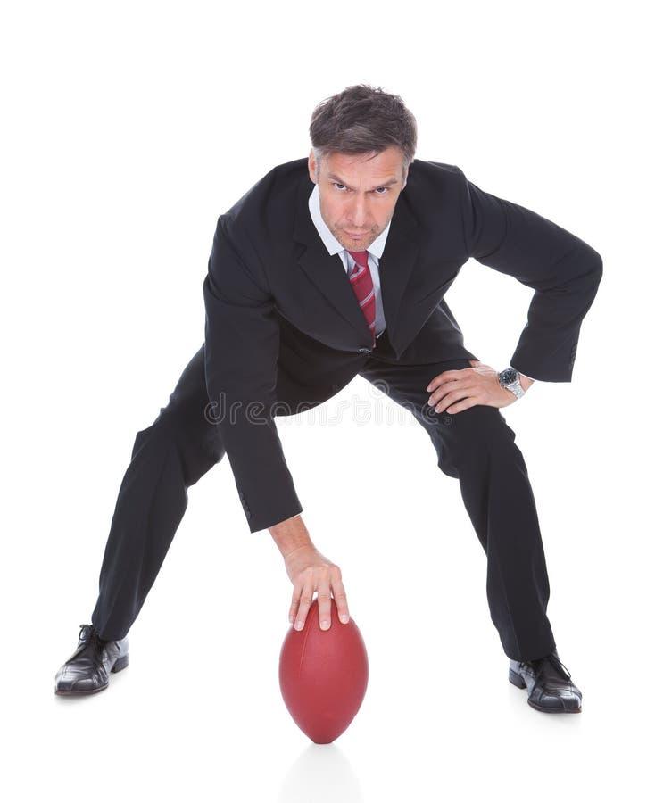Affärsman som spelar rugby arkivfoto