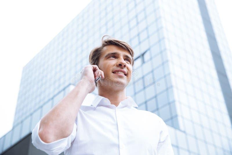 Affärsman som stading nära skyskrapa och talar på mobiltelefonen royaltyfri foto