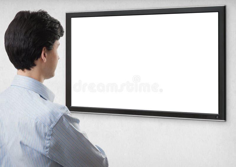 Affärsman som stirrar på tv med den tomma skärmen royaltyfri bild