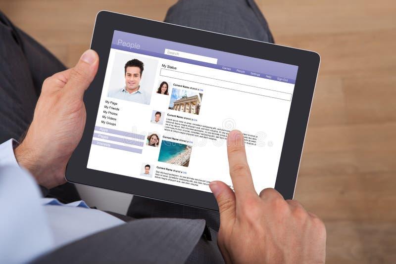 Affärsman som surfar den sociala nätverkandeplatsen på den digitala minnestavlan royaltyfri bild