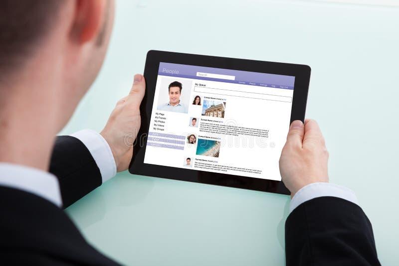 Affärsman som surfar den sociala nätverkandeplatsen på den digitala minnestavlan royaltyfri foto
