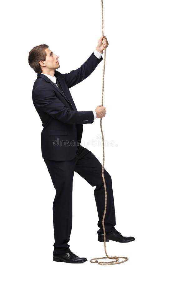 Affärsman som svärmer upp repet arkivfoto