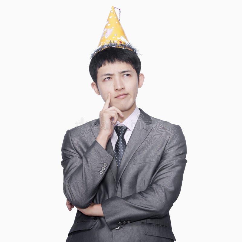 Affärsman som tänker, bärande partihatt, studioskott royaltyfri bild