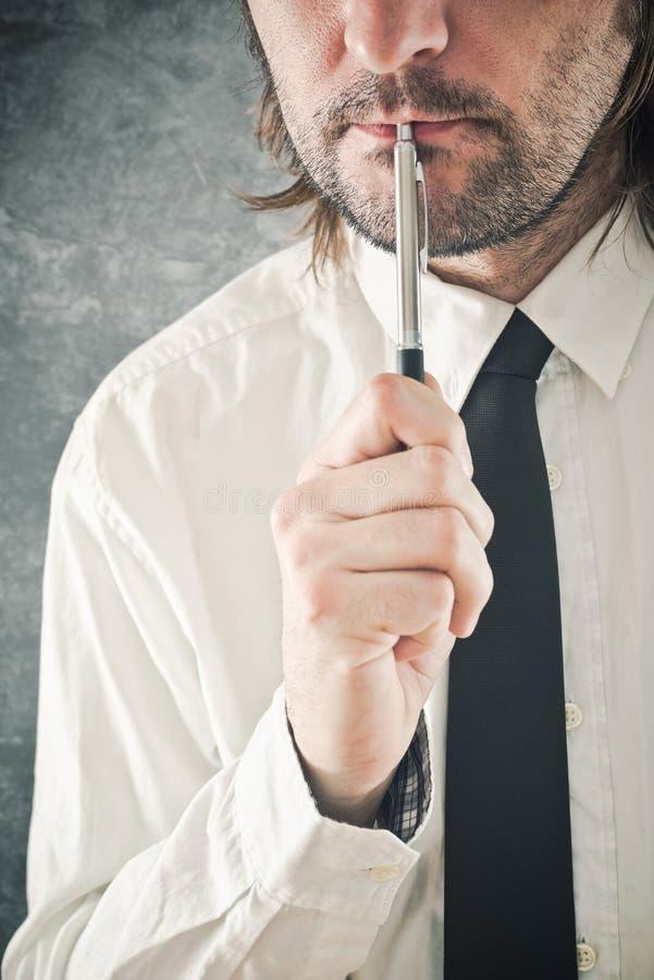 Affärsman som tänker med blyertspennan i hans mun royaltyfria bilder